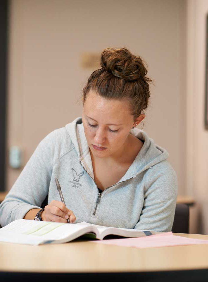 Woman studying and writing notes in college lounge.