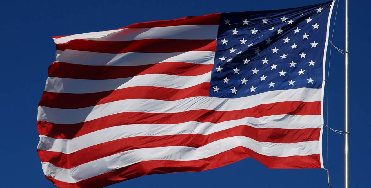the flag of the united states of america, blue rectangle with 50 white stars in the upper left, 13 alternating red and white stripes horizontal everywhere else. Fluttering in a breeze.