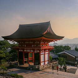 Image of a traditional 日本ese structure at the top of a hill overlooking a scenic valley.