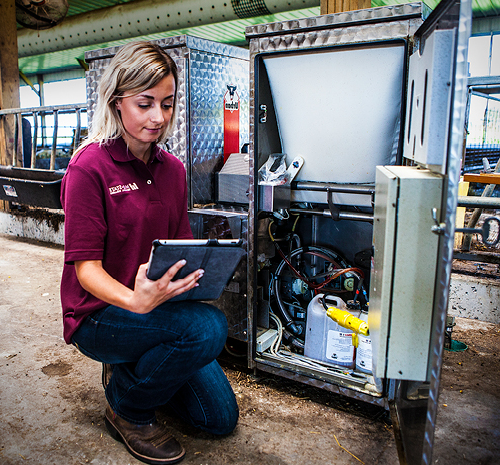 Woman kneeling next to a piece of farming machinery looking at a tablet