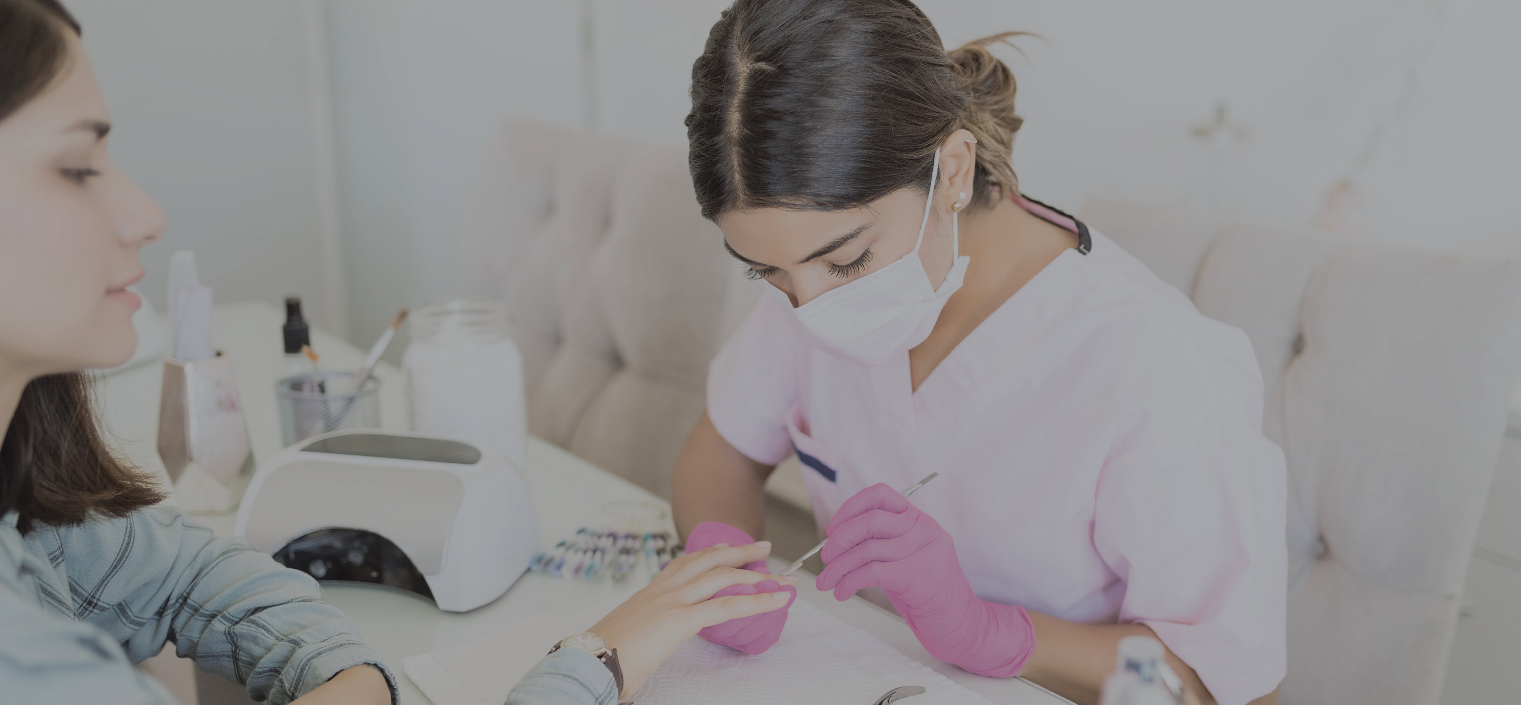 Woman sitting with a mask and gloves on working on another woman's nails who is sitting across from her.